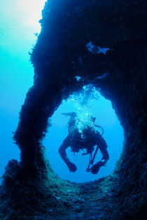 Diver swimming through hole von Sami Sarkis Photography