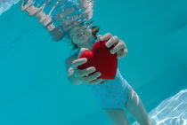 Girl (6-7) holding heart shaped symbol in swimming pool von Sami Sarkis Photography