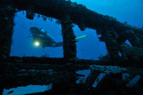 Woman diver with torch exploring shipwreck by Sami Sarkis Photography