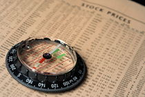 Compass on stockmarket cotation in newspaper by Sami Sarkis Photography