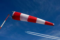 Windsock and airplane against sky by Sami Sarkis Photography