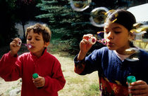Girl and boy blowing bubble-wands by Sami Sarkis Photography