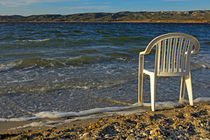 Plastic chair on water edge on beach by Sami Sarkis Photography
