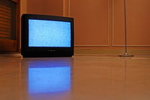 Television displaying static reflected in floor by Sami Sarkis Photography