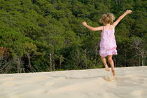 Little girl jumping in sand by Sami Sarkis Photography