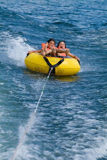 Two children on inflatable ring by Sami Sarkis Photography