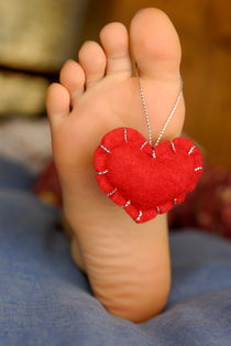 Valentine heart hanging on girl's barefeet von Sami Sarkis Photography