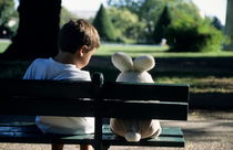 Boy (7-9) sitting on park bench with teddy bear von Sami Sarkis Photography