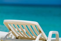 Empty white deck chair on a beach with bright blue waters by Sami Sarkis Photography