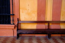 Long wooden bench against a yellow wall at the Alcazar of Seville von Sami Sarkis Photography