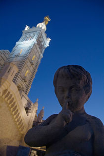 Stone statue of a cherub with view of the bell tower of Notre Dame de la Garde by Sami Sarkis Photography