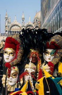 Person surrounded by elaborate masks for sale on St Mark's Basilica von Sami Sarkis Photography