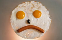 Fried breakfast of eggs and sausage made into a frowning face. von Sami Sarkis Photography