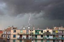 Lightning storm over buildings by Sami Sarkis Photography