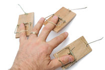 Man's hand with three mousetraps on fingers by Sami Sarkis Photography
