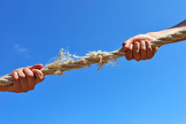 Teenagers hands playing tug-of-war with used rope by Sami Sarkis Photography