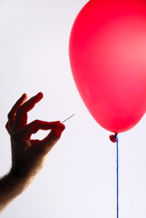 Man's hand with pin next to balloon by Sami Sarkis Photography