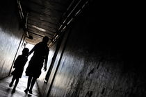 Mother and daughter walking in a dark corridor by Sami Sarkis Photography