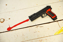 Toy gun on floor with red paint by Sami Sarkis Photography