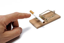 Man's hand about to catch cigarette on mousetrap by Sami Sarkis Photography
