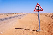 Flood warning sign on desert road by Sami Sarkis Photography