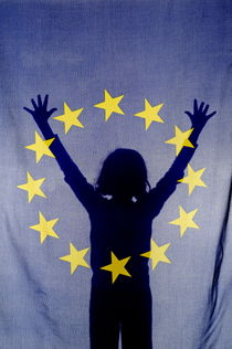 Silhouette of girl with arms raised behind European Union Flag by Sami Sarkis Photography