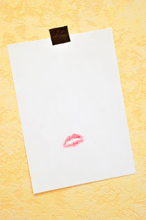 White paper hanged on wall with lipstick kiss von Sami Sarkis Photography