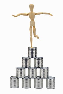Wooden mannequin balancing on top of tin cans pyramid by Sami Sarkis Photography