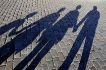 Family of four casting shadows on cobbled stone street by Sami Sarkis Photography