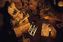 Woman burning candle at Troglodyte Sainte-Marie Madeleine Holy Cave by Sami Sarkis Photography