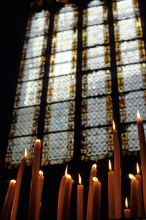 Candles burning in front of a stained glass window in the Auch Cathedral von Sami Sarkis Photography