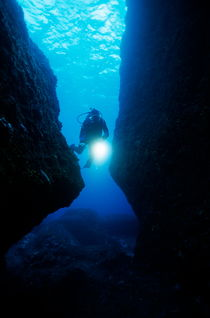 One scuba diver shines an underwater light while swimming through a cave by Sami Sarkis Photography