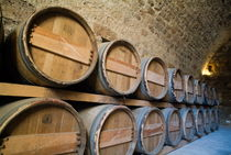 Rows of wooden barrels in the cellar of a castle by Sami Sarkis Photography