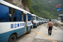 Man searching among a row of tourist buses parked on Mount Hua by Sami Sarkis Photography