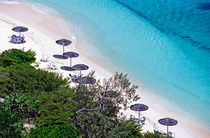 Sun umbrellas dotted along the white sand beach on Amedee Island von Sami Sarkis Photography