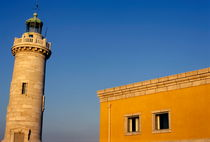 Lighthouse and yellow building at the entrance of the port by Sami Sarkis Photography