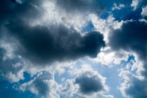 Clouds floating across a blue sky. by Sami Sarkis Photography
