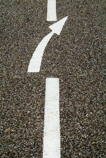 Painted white arrow sign in the dividing line on the road. by Sami Sarkis Photography