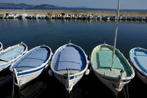 Small fishing boats lined up in a near row by Sami Sarkis Photography