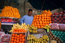 Market vendor selling fruit in a bazaar by Sami Sarkis Photography