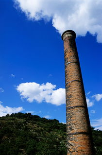 Brick smoke stack emitting smoke von Sami Sarkis Photography