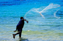 Man launching his fishing net into the crystal water by Sami Sarkis Photography