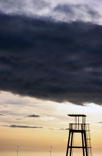 Storm clouds gathering over a lifeguard tower at sunset by Sami Sarkis Photography
