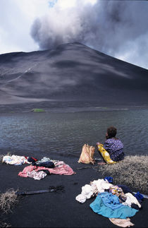 Girl washing clothes in a lake with the Mount Yasur volcano emitting smoke in the background by Sami Sarkis Photography