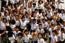 Bangkok school children jumping and smiling at the camera von Sami Sarkis Photography