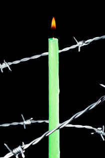 Lit candle surrounded by barbed wire. by Sami Sarkis Photography