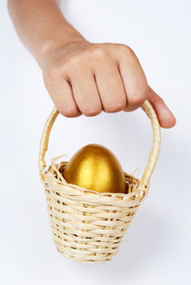 Girl's hand holding basket with golden egg von Sami Sarkis Photography
