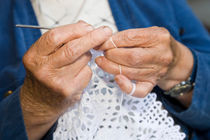 Old woman crocheting by kbhsphoto