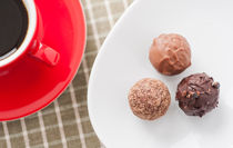 Three chocolate truffles and a red coffee cup von Lars Hallstrom